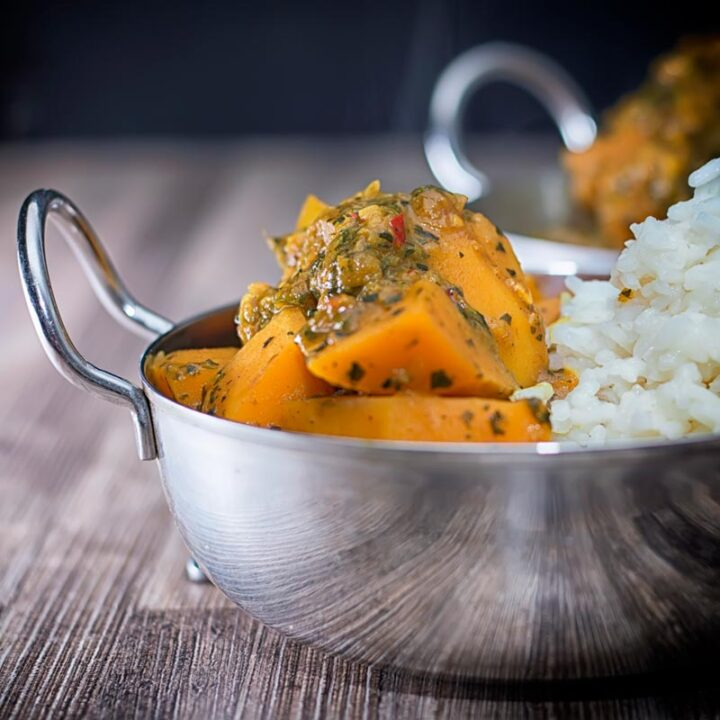 Square image of a steaming hot pumpkin curry with white rice served in a stainless steel curry bowl