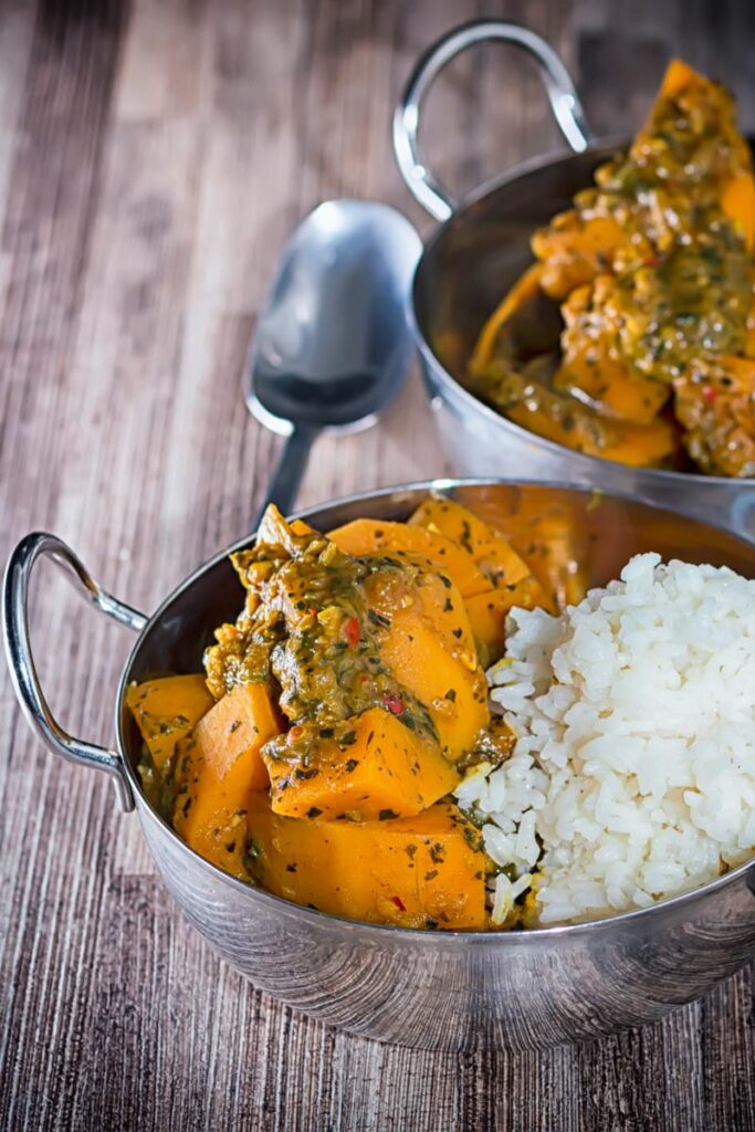 Portrait image of a pumpkin curry with white rice served in two stainless steel curry bowls