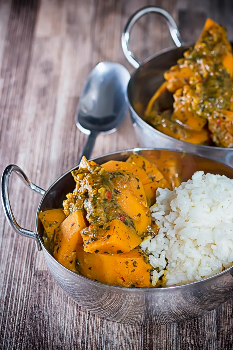 Portrait image of a pumpkin curry with white rice served in a two stainless steel curry bowls