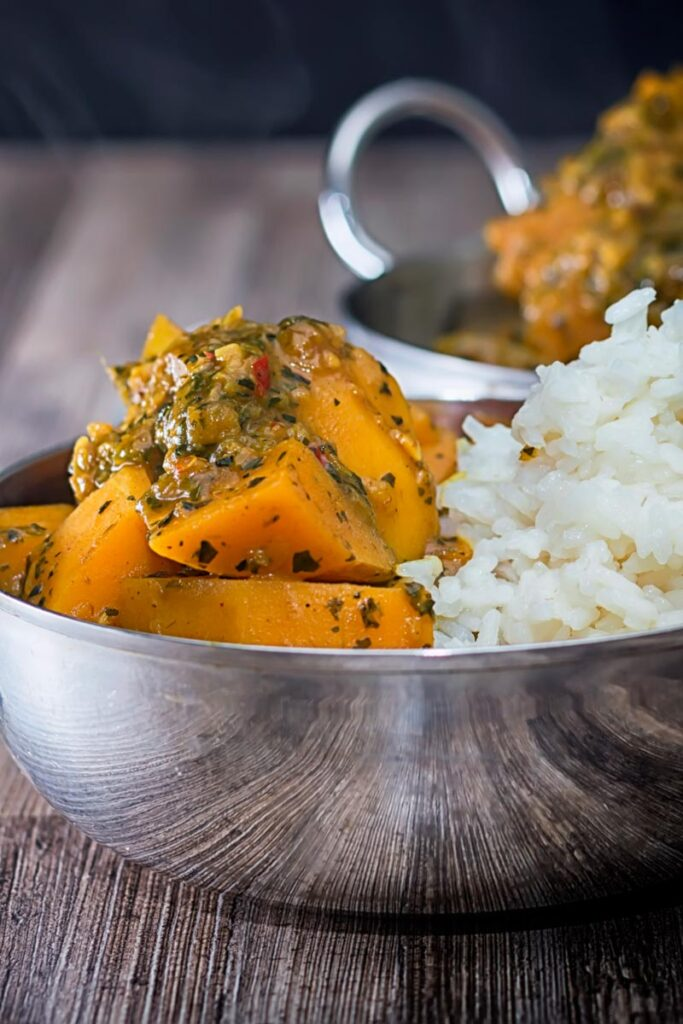 Portrait image of a steaming hot pumpkin curry with white rice served in a stainless steel curry bowl