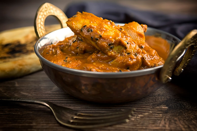 Landscape image of a chicken jalfrezi curry in a copper coated curry bowl served with a naan bread