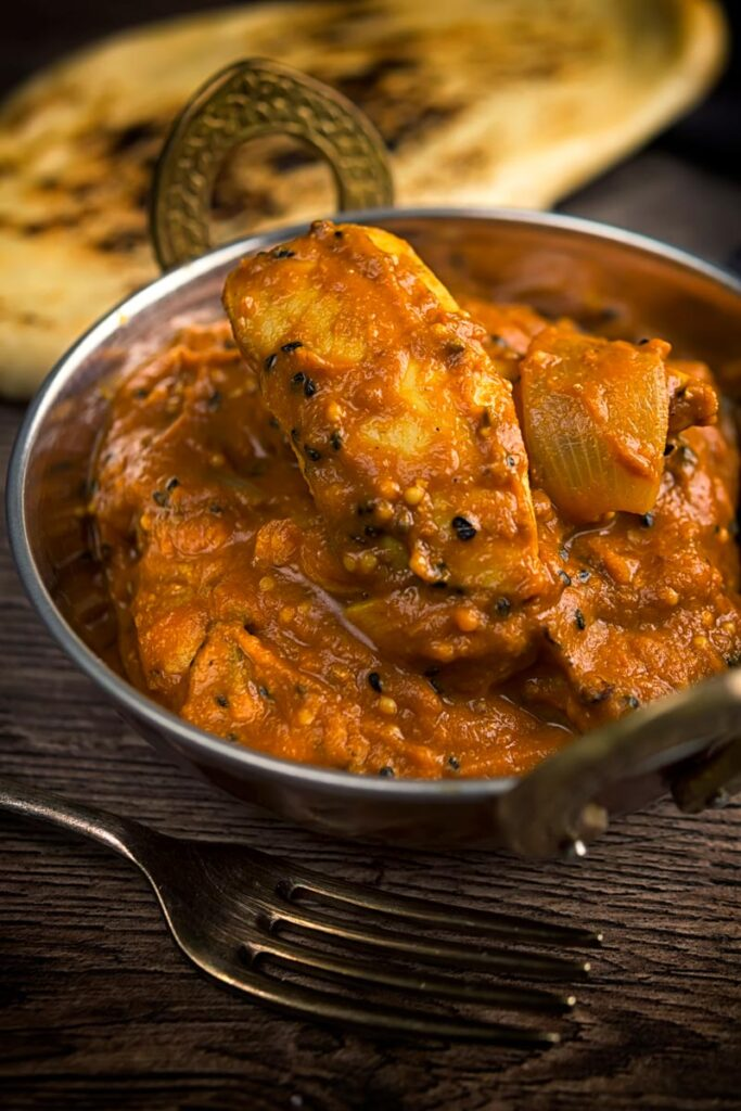 Portrait image of a chicken jalfrezi curry in a copper coated curry bowl served with a naan bread