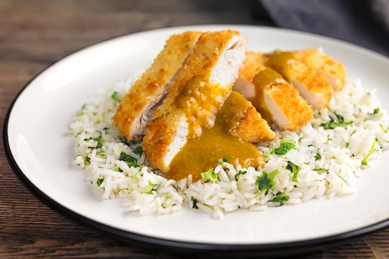 Landscape image of chicken katsu curry served on coriander rice on a white plate