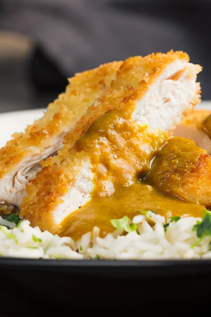 Portrait close up image of chicken katsu curry served on coriander rice on a white plate