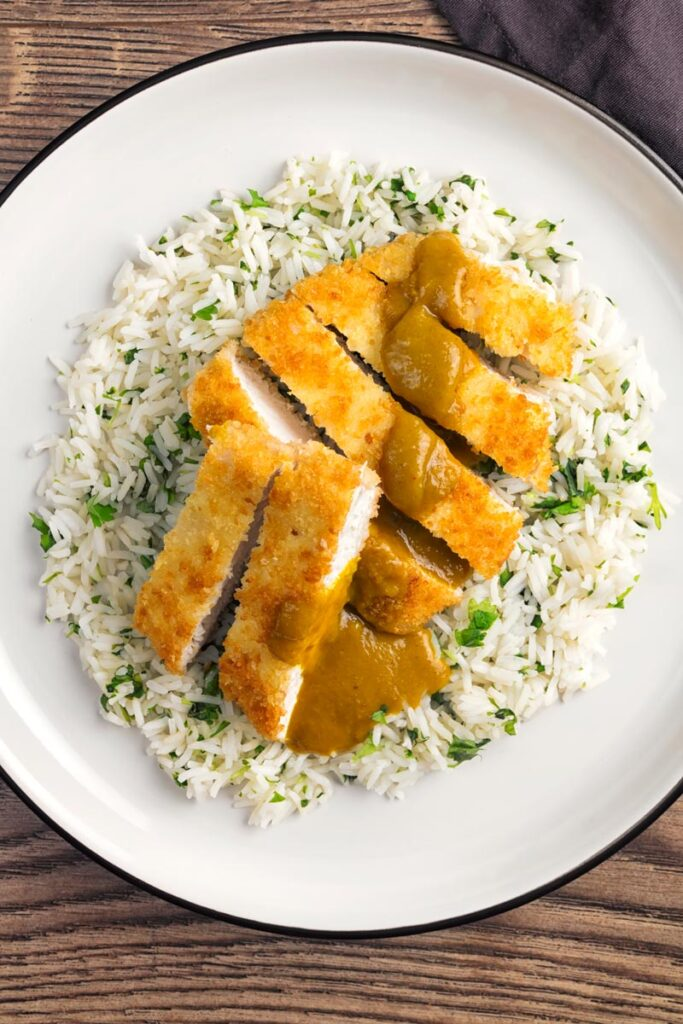 Portrait overhead image of chicken katsu curry served on coriander rice on a white plate