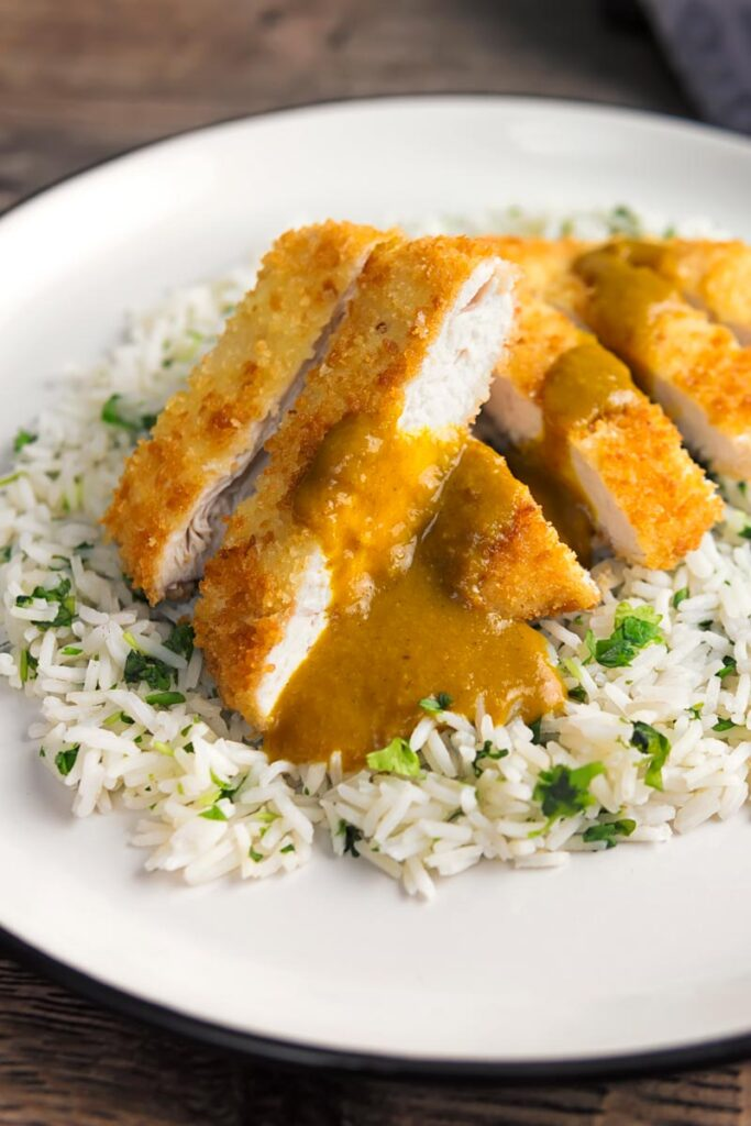 Portrait image of chicken katsu curry served on coriander rice on a white plate