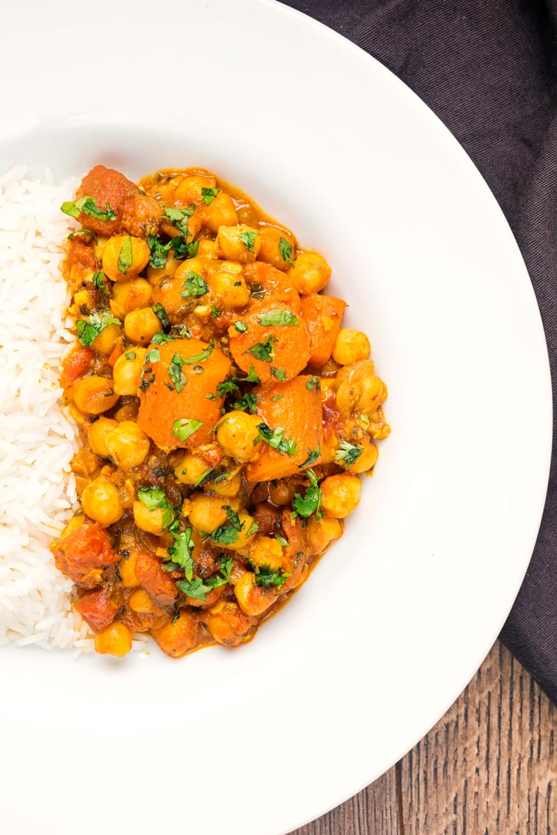 Overhead portrait image of a chickpea and carrot curry served with basmati rice served in a white bowl.