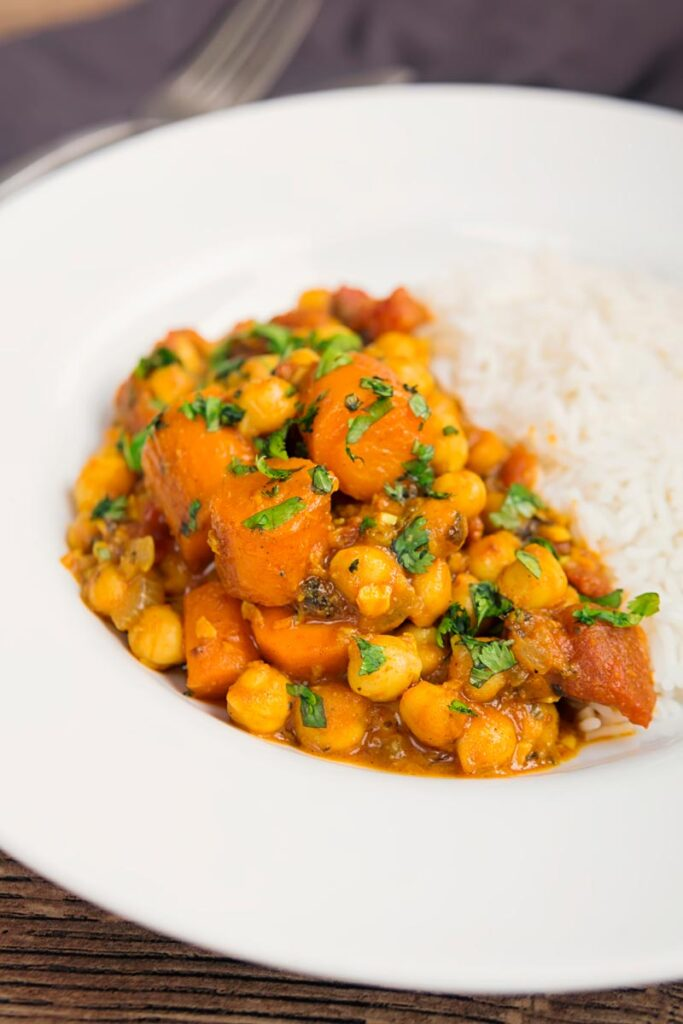 Portrait image of a chickpea and carrot curry served with basmati rice and fresh coriander served in a white bowl