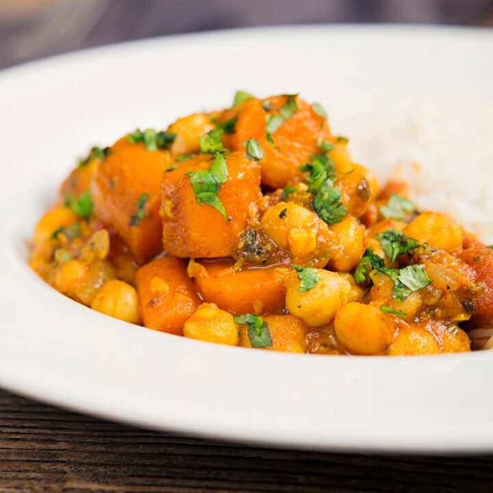 Square image of a chickpea and carrot curry served with basmati rice and fresh coriander served in a white bowl