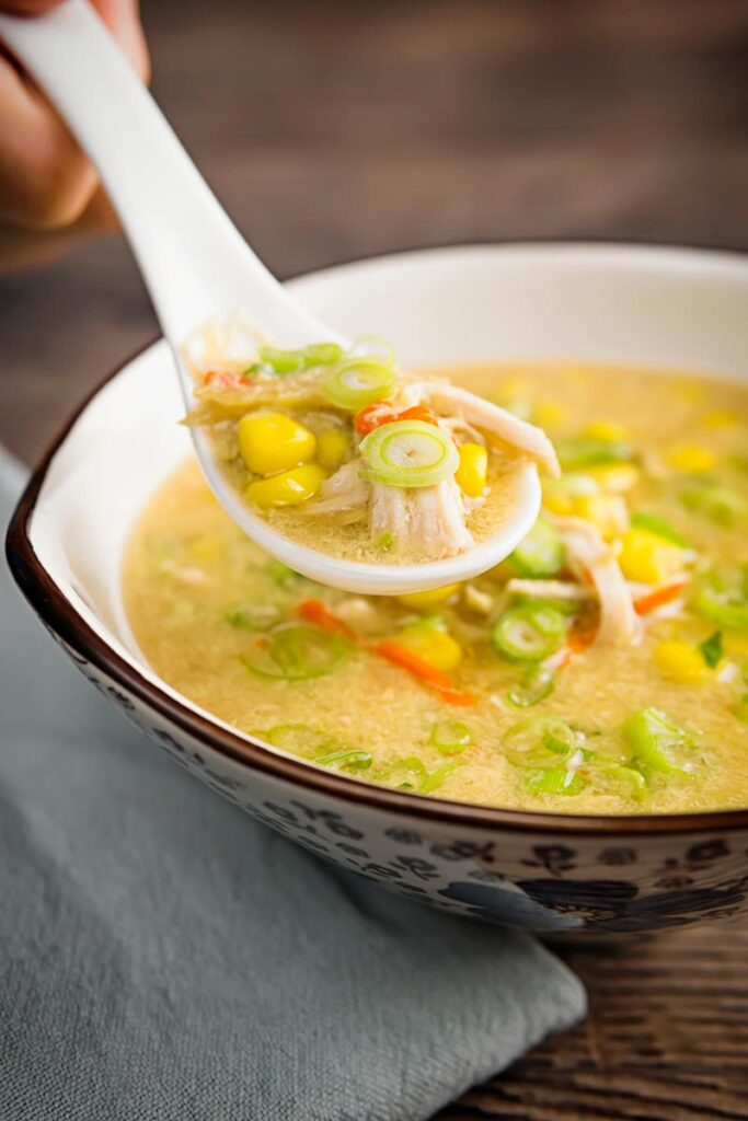 Portrait image of a Chinese chicken and sweetcorn soup served in an asian bowl with a portion on a porcelain spoon