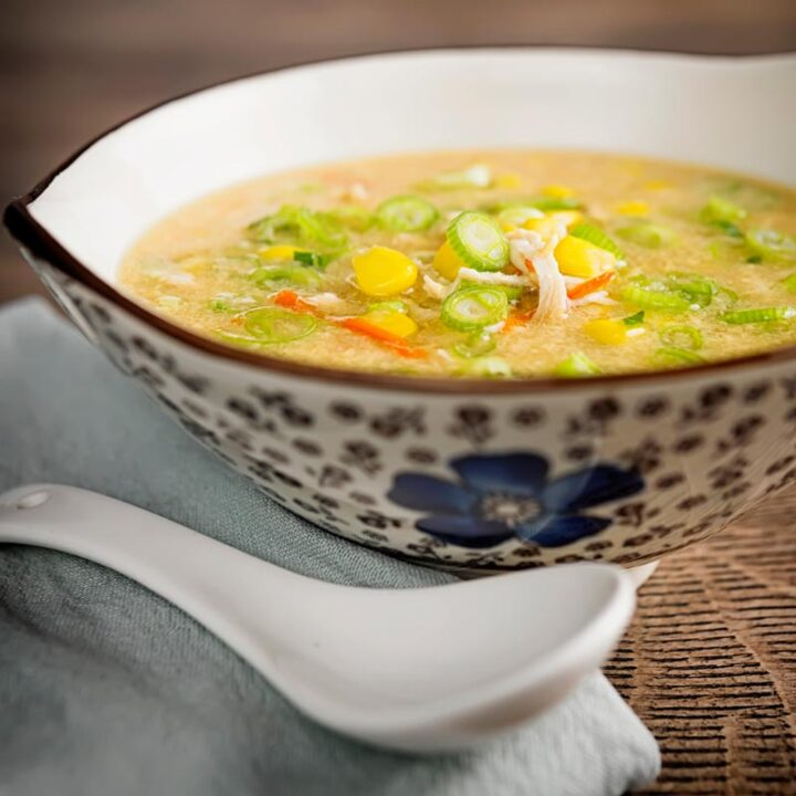 Square image of a Chinese chicken and sweetcorn soup served in an asian bowl