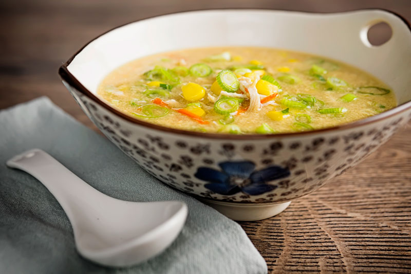 Landscape image of a Chinese chicken and sweetcorn soup served in an asian bowl