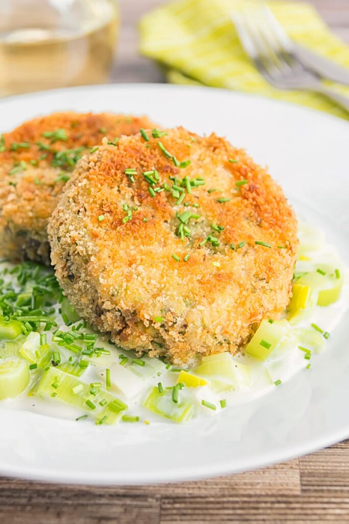 Portrait image of classic creamed leeks served on a white plate with fishcakes