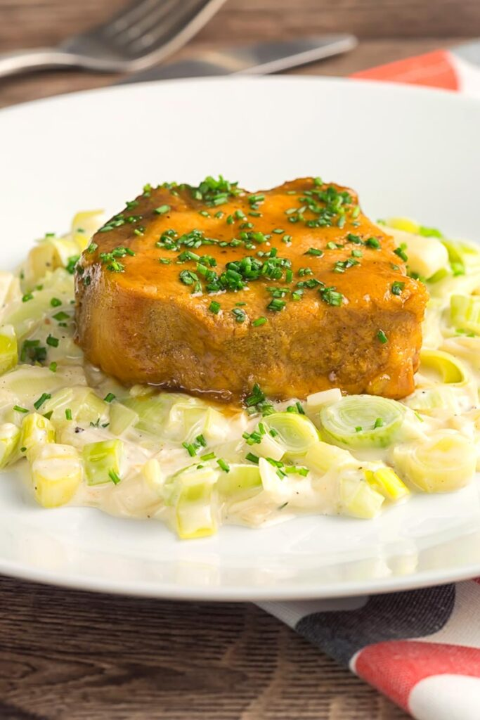 Portrait image of classic creamed leeks served on a white plate with glazed pork loin