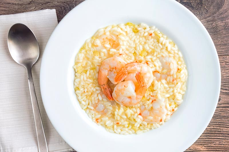 Landscape image of a lemon and chilli prawn risotto featuring 3 shrimp with tails on served in a white bowl
