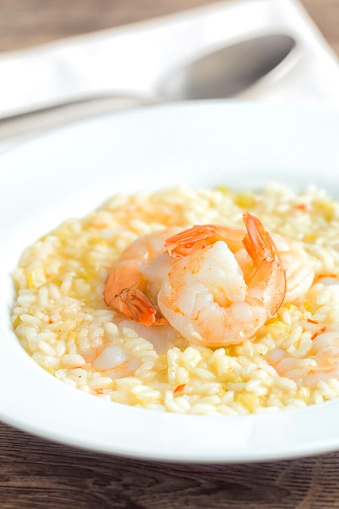 Portrait image of a lemon and chilli prawn risotto featuring 3 shrimp with tails on served in a white bowl