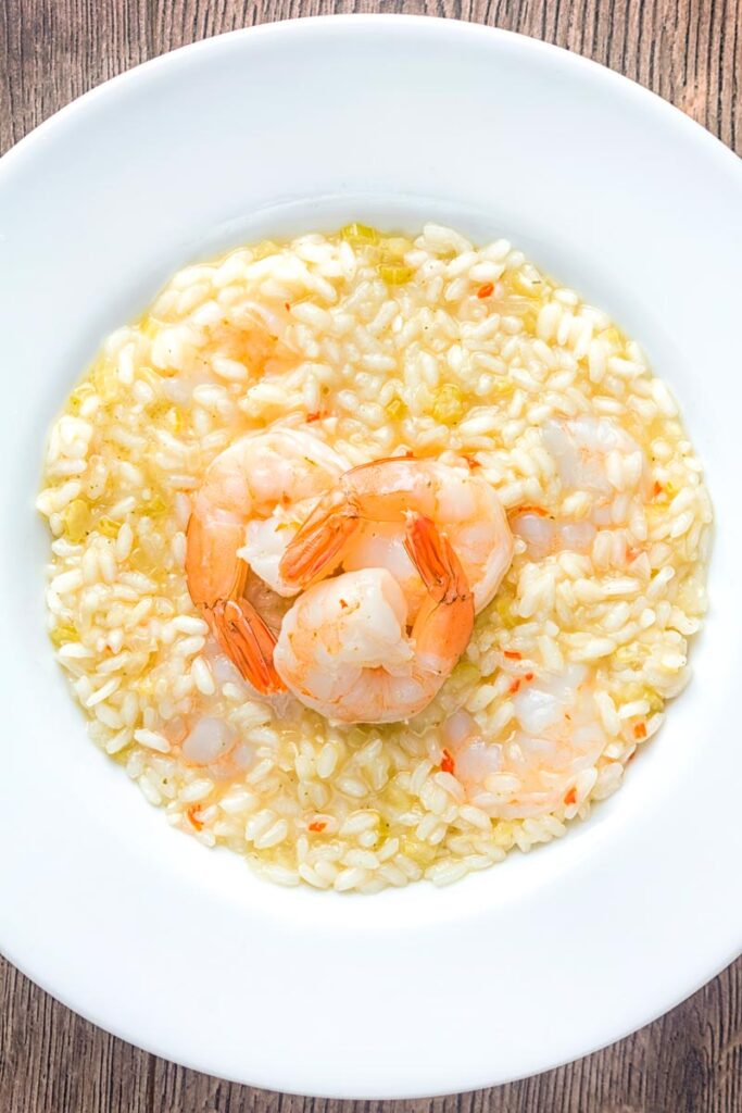 Portrait overhead image of a lemon and chilli prawn risotto featuring 3 shrimp with tails on served in a white bowl