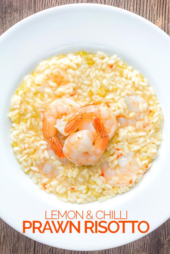 Portrait overhead image of a lemon and chilli prawn risotto featuring 3 shrimp with tails on served in a white bowl with text overlay