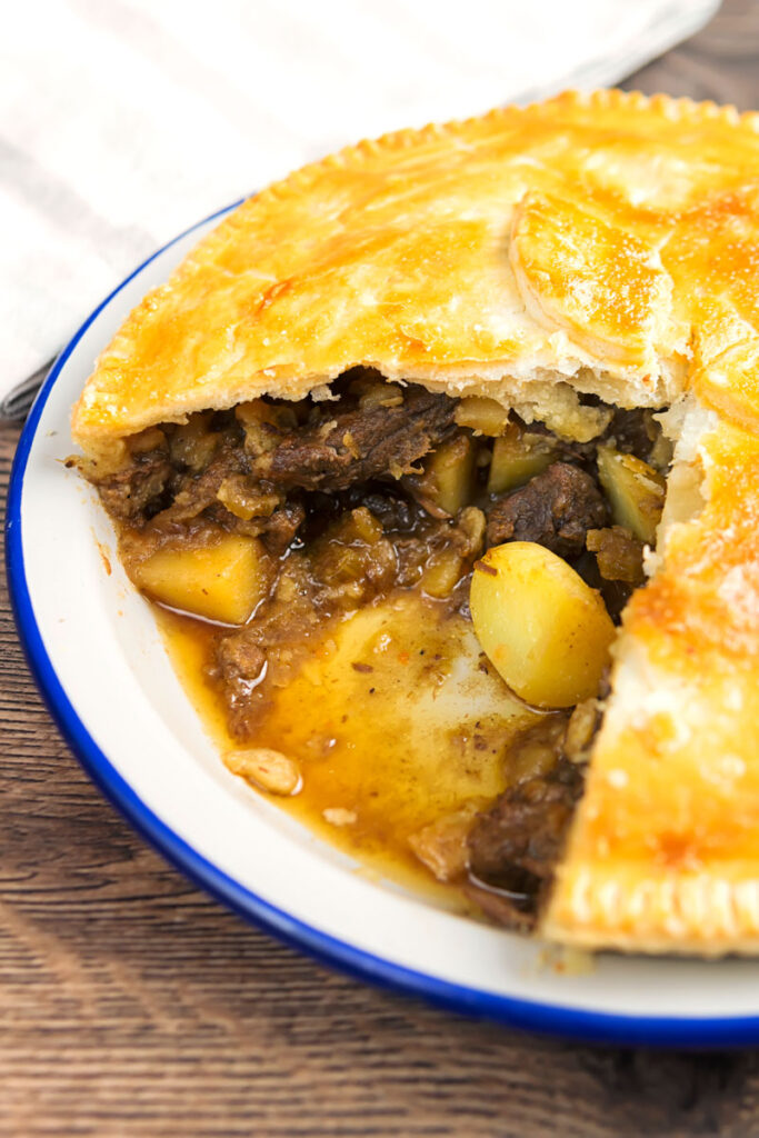 Portrait image of a meat and potato pie cooked in an enamel plate with a slice removed showing pie filling