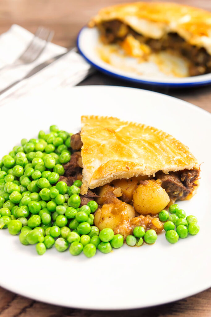 Portrait image of a slice of meat and potato pie served with garden peas on a white plate with the pie out of focus behind