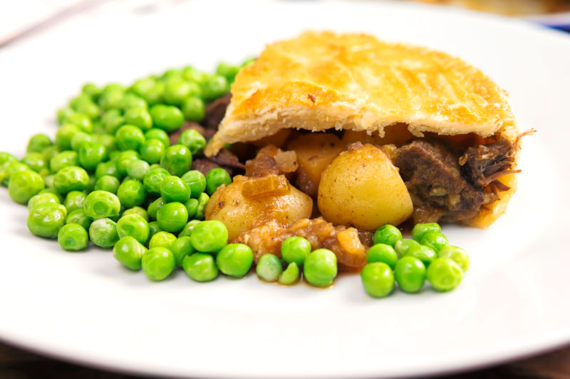 Landscape image of a slice of meat and potato pie served with garden peas on a white plate
