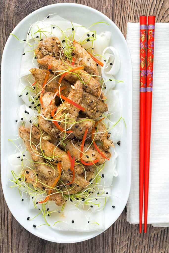 Overhead portrait image of salt and pepper chicken with pickled daikon and sprouted onion seeds with red chopsticks