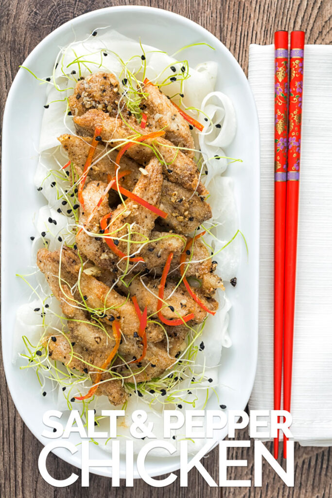 Overhead portrait image of salt and pepper chicken with pickled daikon and sprouted onion seeds with red chopsticks with text overlay