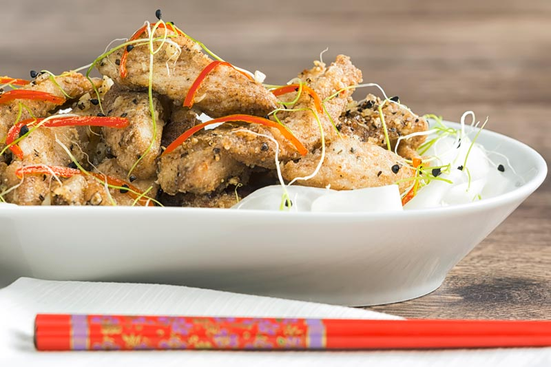 Landscape image of salt and pepper chicken with pickled daikon and sprouted onion seeds with red chopsticks