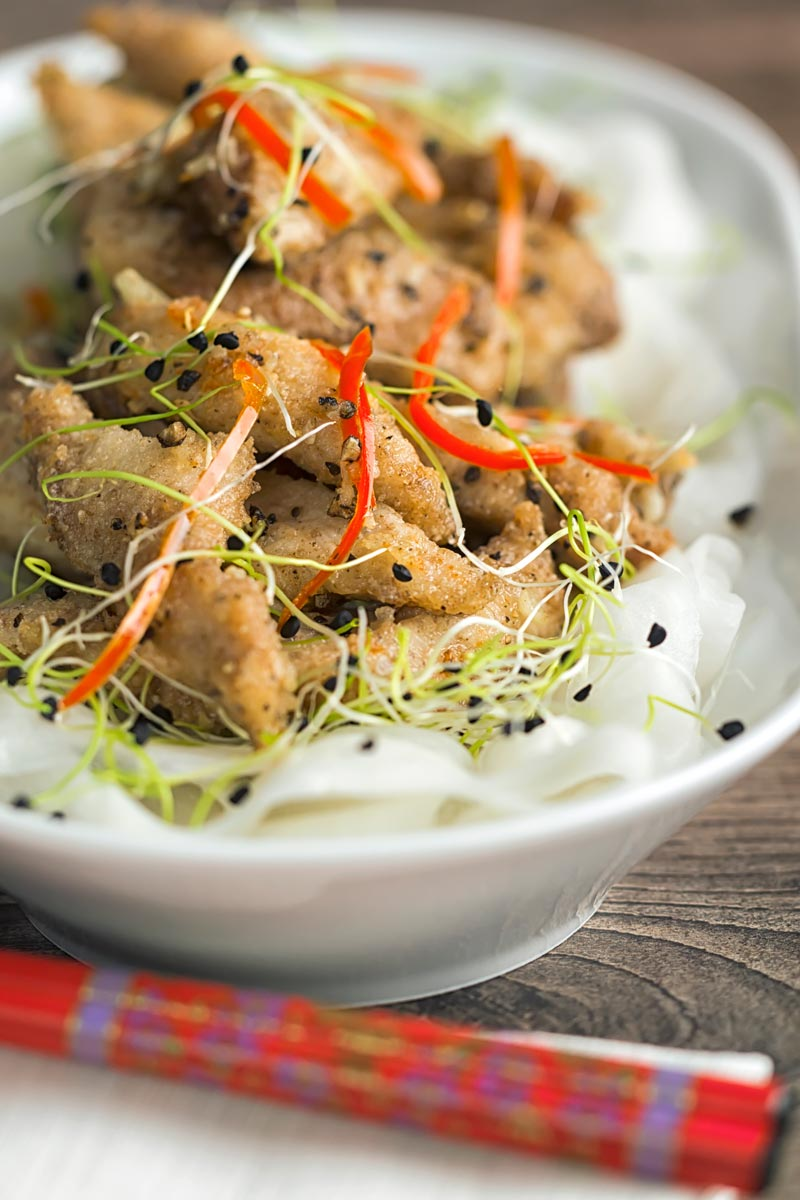 Portrait image of salt and pepper chicken with pickled daikon and sprouted onion seeds with red chopsticks