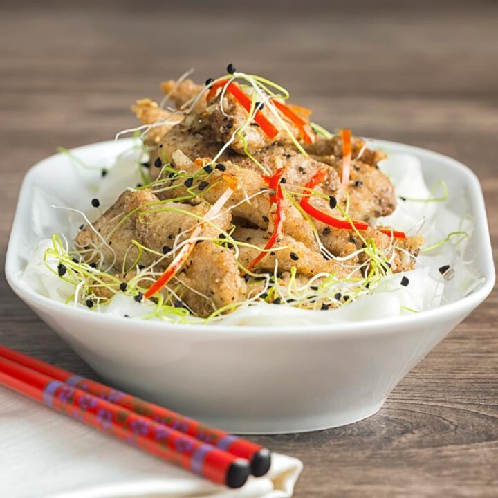Square image of salt and pepper chicken with pickled daikon and sprouted onion seeds with red chopsticks