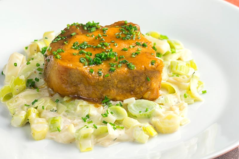 Landscape image of a portion of slow cooker pork loin that has been sliced served with creamed leeks on a white plate