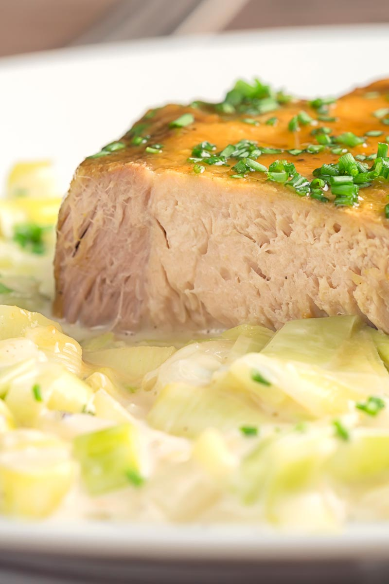 Portrait close up image of a portion of slow cooker pork loin that has been sliced served with creamed leeks on a white plate