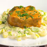 Portrait image of a portion of slow cooker pork loin served with creamed leeks on a white plate with a text overlay