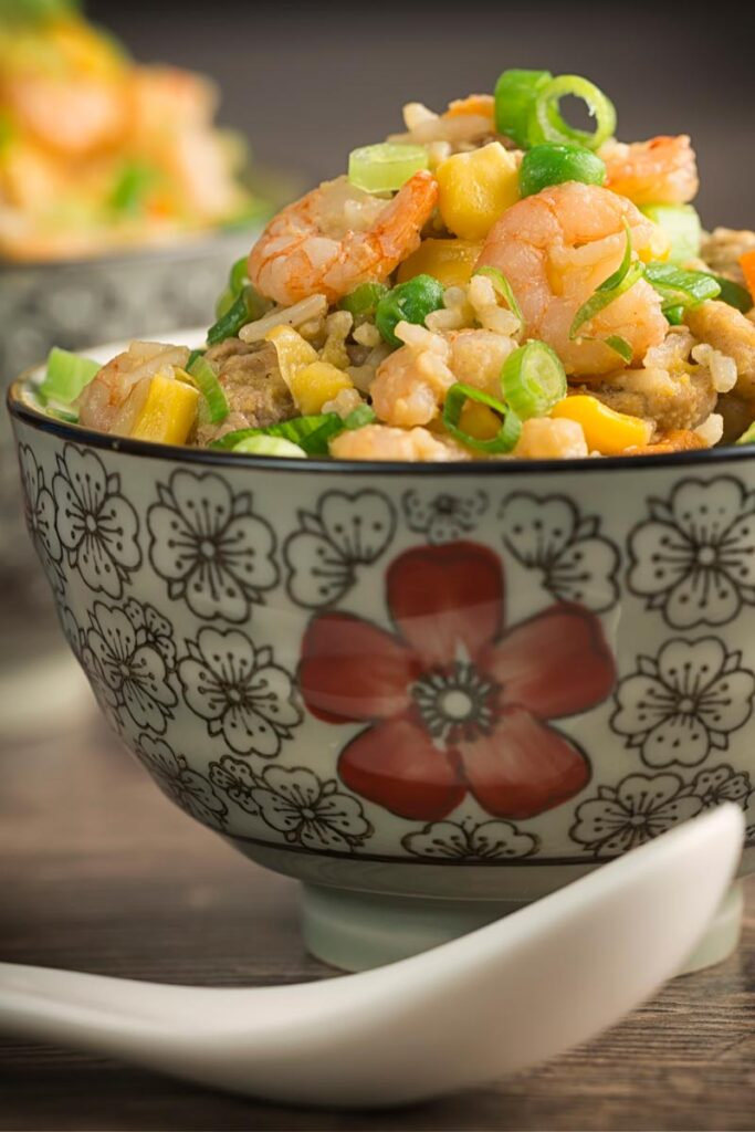 Portrait image of house special fried rice served in an Asian style bowl decorated with a red flower