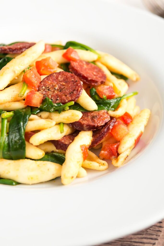 Portrait image of spinach and chorizo pasta with diced tomatoes and capunti pasta