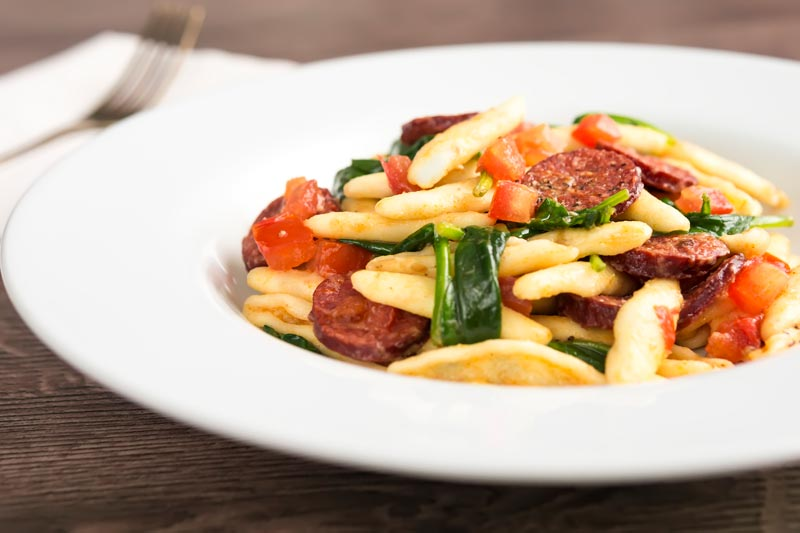 Landscape image of spinach and chorizo pasta with diced tomatoes and capunti pasta
