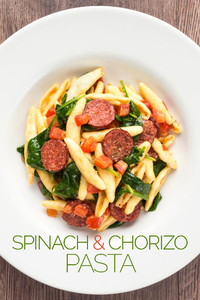 Portrait overhead image of spinach and chorizo pasta with diced tomatoes and capunti pasta with text overlay