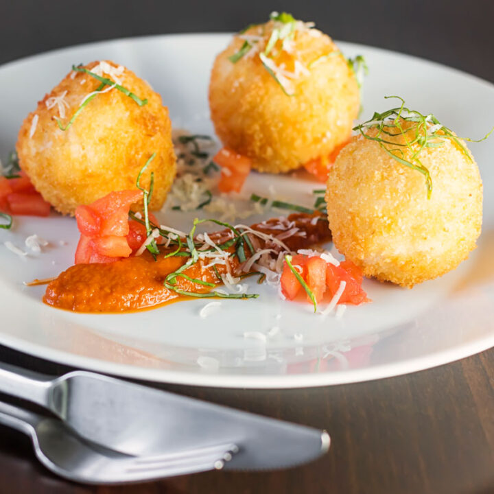 Square image of three golden stuffed arancini balls served on a white plate with tomato sauce, tomato concase and shredded basil