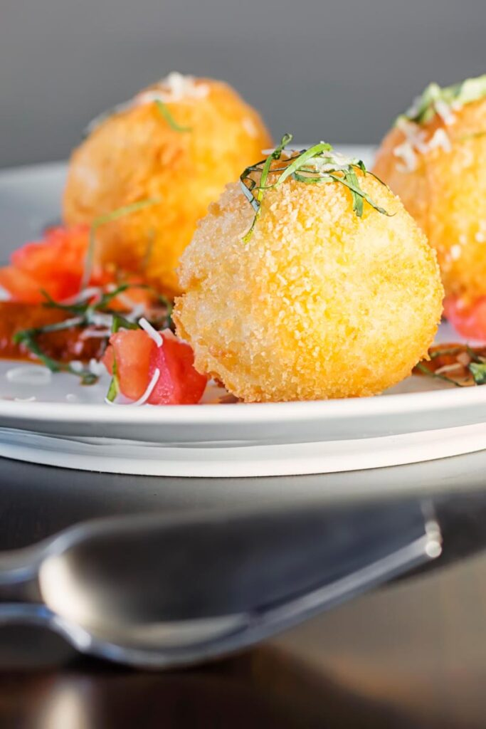 Portrait close up image of three golden stuffed arancini balls served on a white plate with tomato sauce, tomato concase and shredded basil
