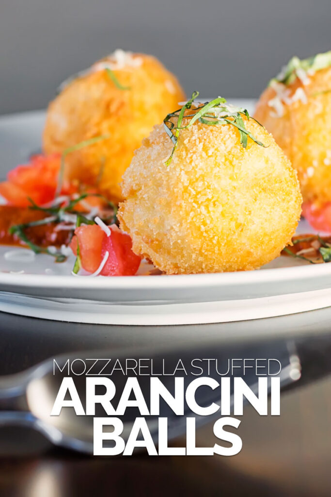 Portrait close up image of three golden stuffed arancini balls served on a white plate with tomato sauce, tomato concase and shredded basil with text overlay