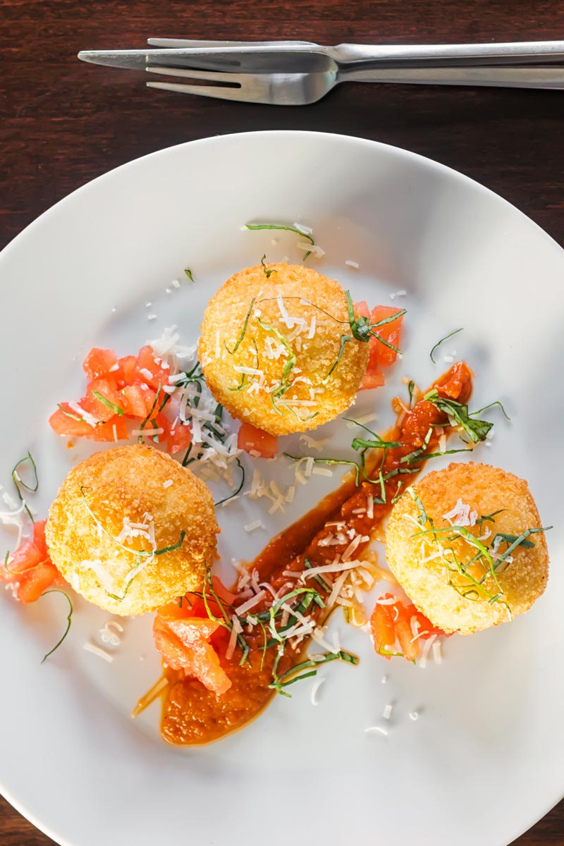 Portrait overhead image of three golden stuffed arancini balls served on a white plate with tomato sauce, tomato concasse and shredded basil