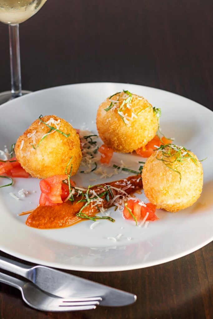 Portrait image of three golden stuffed arancini balls served on a white plate with tomato sauce, tomato concasse and shredded basil