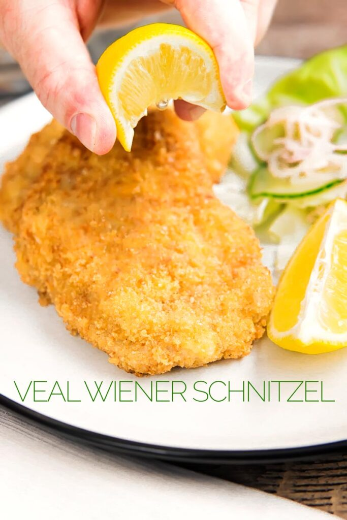 Portrait image of a lemon wedge being squeezed over a classic breaded veal Wiener schnitzel served with a classic green salad on a white plate with a text overlay