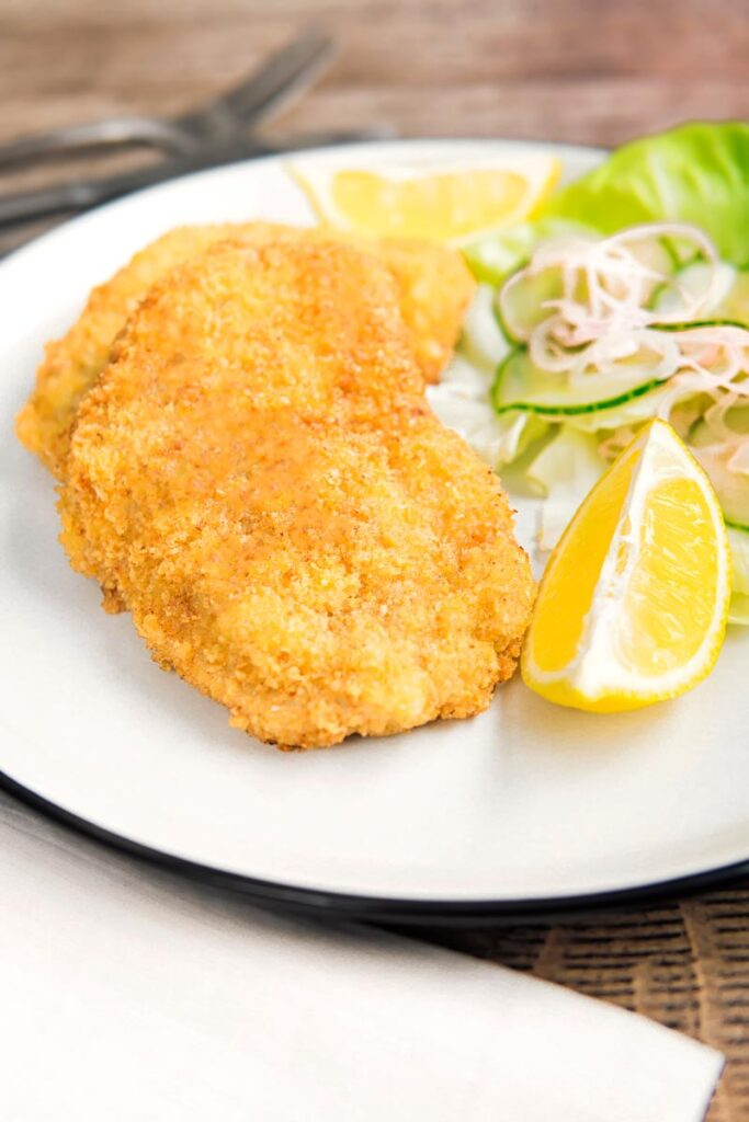 Portrait image of a classic breaded veal Wiener schnitzel served with a classic green salad on a white plate