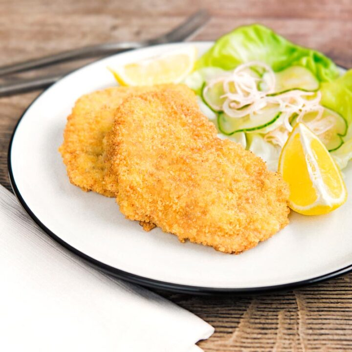 Square image of a classic breaded veal Wiener schnitzel served with a classic green salad on a white plate