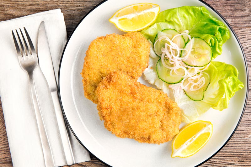 Landscape overhead image of a classic breaded veal Wiener schnitzel served with a classic green salad and lemon wedges on a white plate