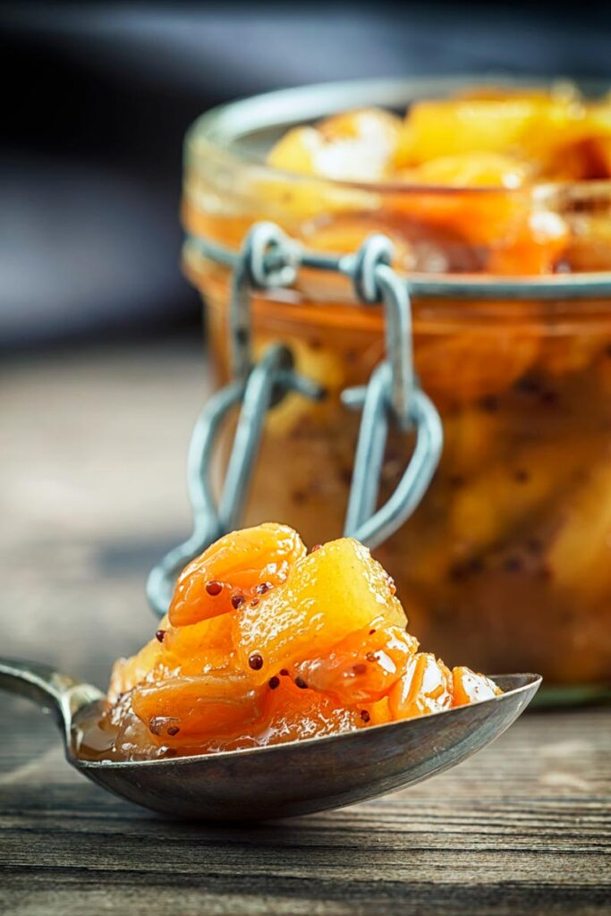 Portrait image of a spoonful of chunky apple chutney with an out of focus jar of chutney in the background