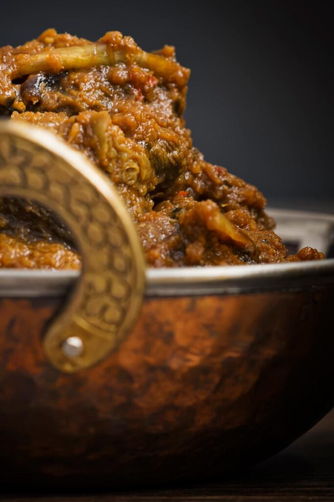 Close up portrait image of a beef dopiaza curry served in a hammered copper coloured curry bowl