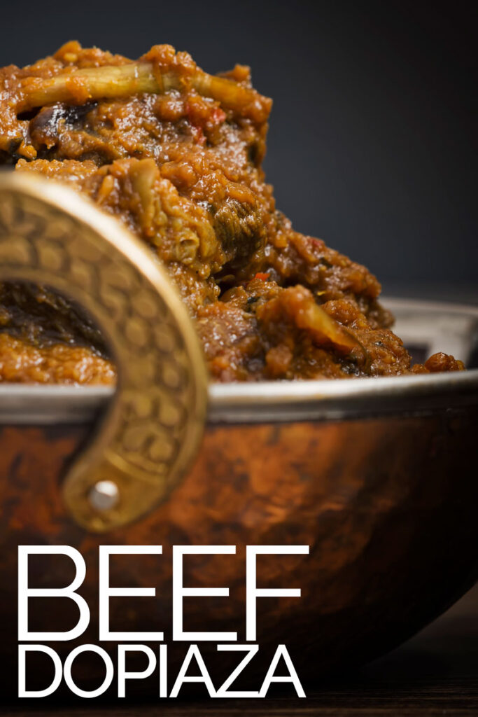 Portrait close up image of a beef dopiaza curry served in a hammered copper coloured curry bowl with text overlay