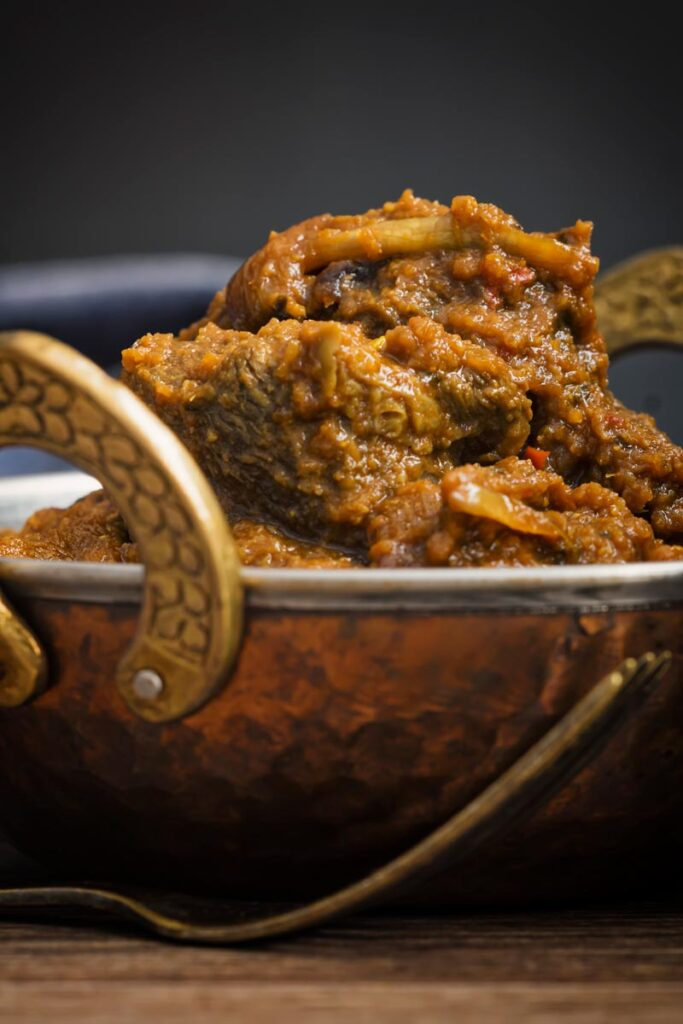Portrait partial image of a beef dopiaza curry served in a hammered copper coloured curry bowl
